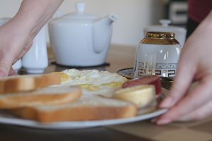 Female hands serving traditional breakfast meal - fried eggs and toast. Putting porcelain plate with eat on wooden table. Close up