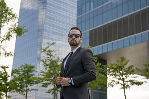 Businessman looking and buckling jacket