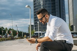 Businessman with sunglasses and smartphone