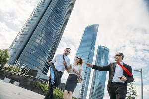 A woman and two businessmen walking and fun