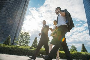 A woman and two businessmen walking