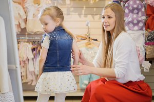 Shopping for kids. The girl looks at herself in the mirror