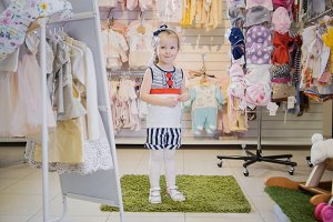 A girl trying on a striped suit in a children's clothing store