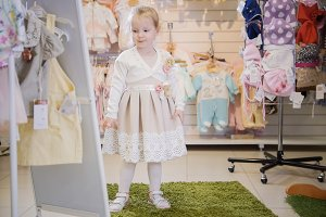 A sweet girl trying on a smart dress in a children's clothing store