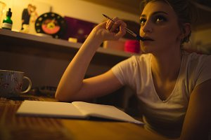 Woman thinking while writing notes in drawing room