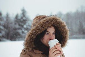 Beautiful woman in fur jacket having coffee