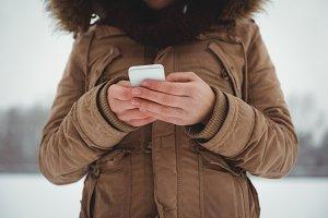 Woman in fur jacket using mobile phone