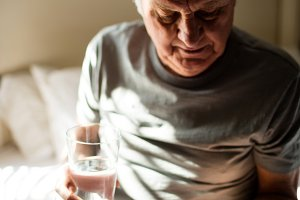 Senior man taking medicine in the bedroom