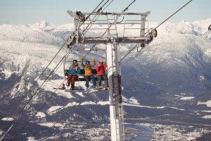 Three skiers travelling in ski lift at ski resort