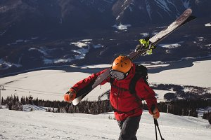 Skier walking in snow alps with ski