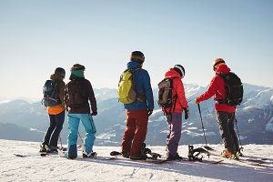 Group of skiers standing on top of the mountain