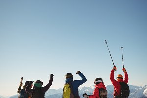 Celebrating skiers standing on snow covered mountain
