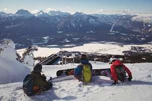 Three skiers relaxing on snow landscape