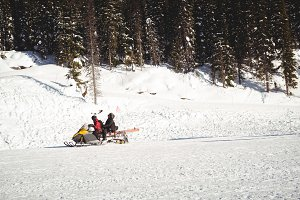 Skiers riding snowmobile in snowy alps