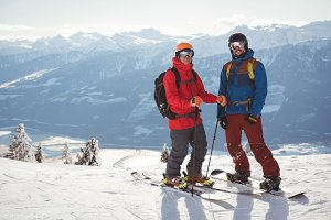 Two skiers standing together on snow covered mountain