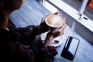 Woman holding cup of coffee in café
