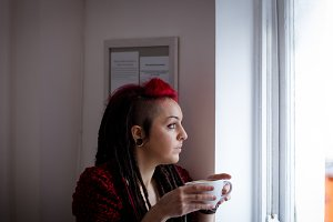 Woman looking through window while having coffee