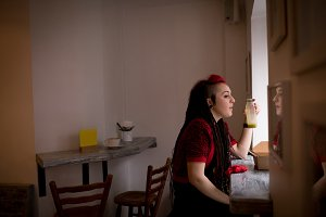 Beautiful woman looking through window while having health drink