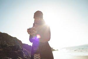 Woman looking at photos on digital camera at beach