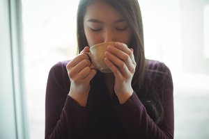 Woman having cup of coffee at café