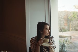 Woman having cup of coffee near window at café