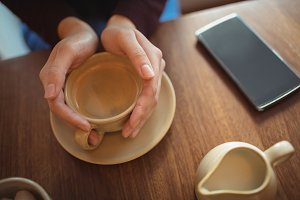 Mid section of woman holding a coffee cup