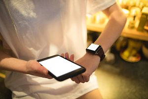 Woman using smart watch while holding smartphone