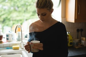 Thoughtful woman holding a coffee cup in kitchen