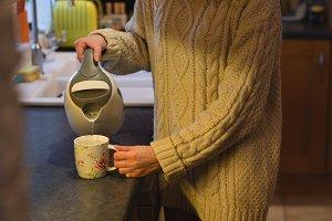 Woman preparing coffee in kitchen