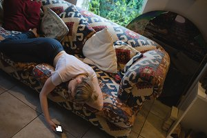 Woman lying and using mobile phone on couch in living room