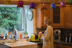Woman holding a coffee cup in kitchen