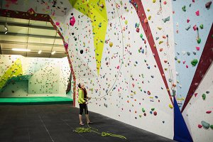 Trainer holding the rope near artificial climbing wall