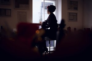 Woman looking through window in café