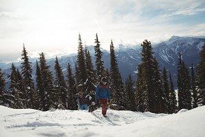 Men running on snow covered mountain