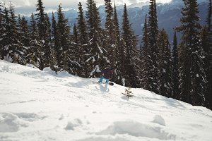 Person snowboarding on mountain during winter