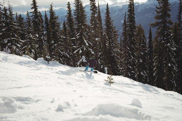Person snowboarding on mountain dur…