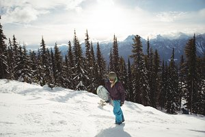 Woman holding snowboard on mountain during winter
