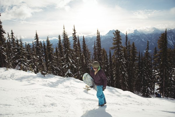 Woman holding snowboard on mountain…