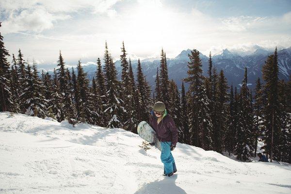Woman holding snowboard on mountain…