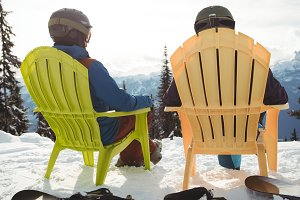 Rear view of couple sitting on mountain during winter