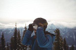 Man wearing helmet at mountain during winter