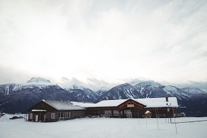 Houses on snow covered field by mountains