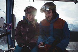 Couple using mobile phone while sitting in overhead cable car