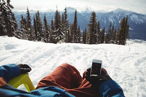 Low section of man holding mobile phone at snow covered mountain