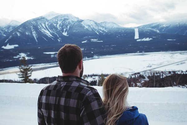 Couple standing on snow covered fie…