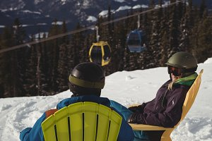 Couple sitting on chair at snow covered mountain