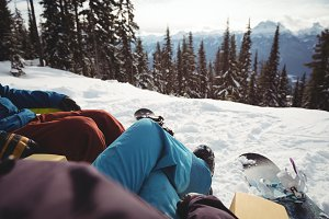 Couple sitting at snow covered mountain