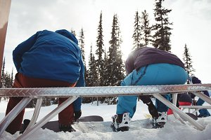 Rear view of couple sitting on bench at mountain during winter