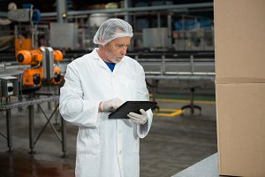 Male worker using digital tablet in cold drink factory