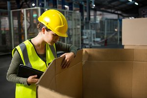 Female worker checking products at warehouse